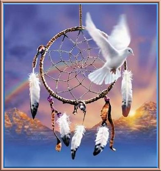Dreamcatcher, dove, and rainbow over mountains