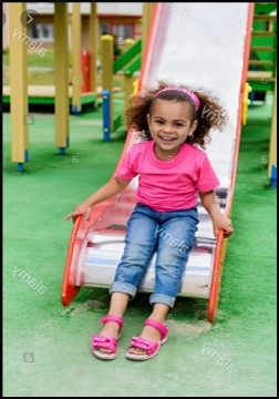 Happy black child sitting at a slide bottom with her feet on the ground